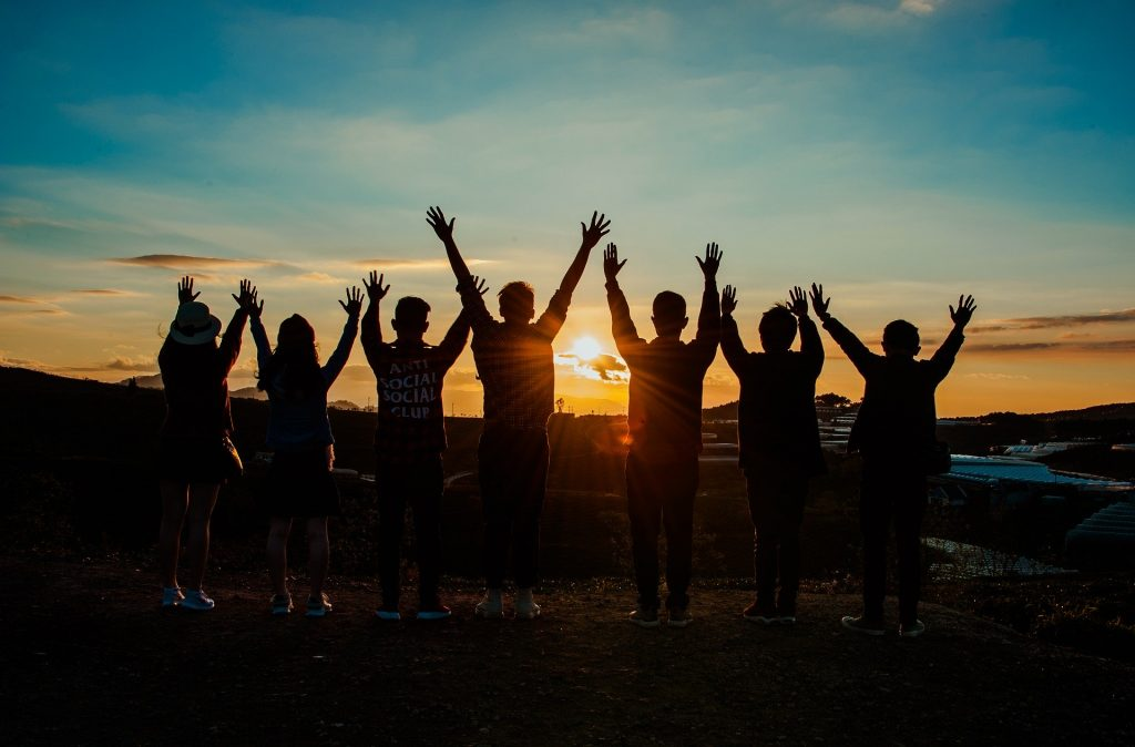 Silouette of people with arms stretched up as sun sets