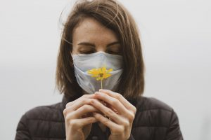 woman contemplating flower while wearing a face mask